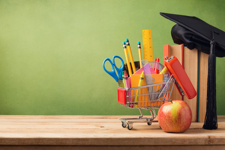 Back to school concept with shopping cart, books and graduation hat Foto de archivo