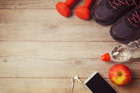 Fitness background with bottle of water, dumbbells and athletic shoes. View from above