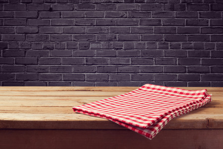 tablecloth: Wooden counter background with red checked tablecloth over black brick wall Stock Photo