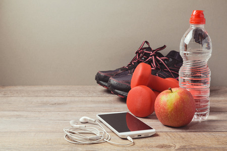 Fitness concept with dumbbells, apple and smartphone Stok Fotoğraf