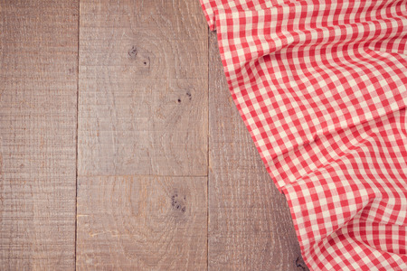 Wooden board background with red checked tablecloth. View from above