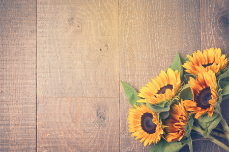Autumn background with sunflowers on wooden table. View from above. Retro filter effect