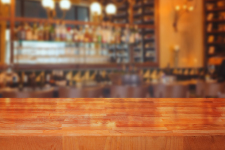 bar interior: Wooden table over blurred bar interior