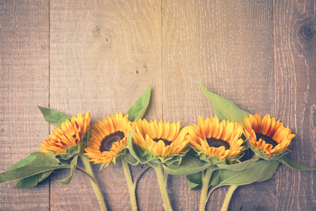 Autumn background with sunflowers on wooden board. View from above. Retro filter effect
