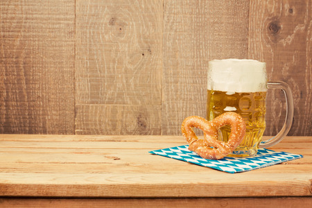 Oktoberfest german beer festival  background with beer glass and pretzel on wooden table