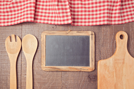 utencils: Abstract wooden background with red checked tablecloth, chalkboard and kitchen utencils. View from above