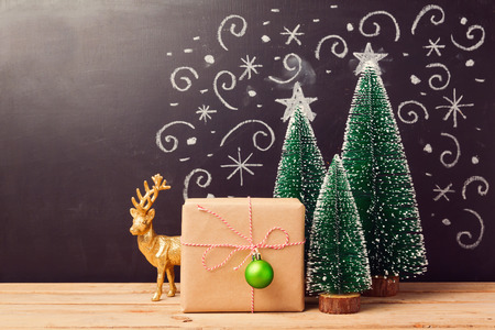 Christmas decorations and gift box over chalkboard background
