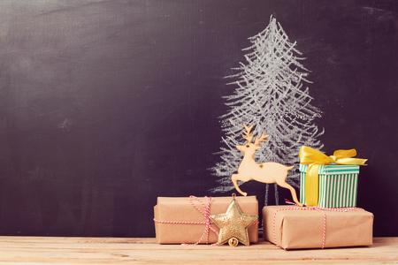 黒板上に描画の木の下でクリスマス ギフト ボックス。代替のクリスマス ツリーの背景色