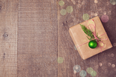 wrappings: Christmas gift box with decorations on wooden background. View from above with copy space