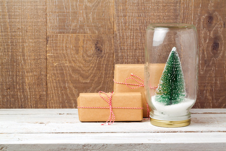 Christmas gift boxes and tree in glass jar over wooden background