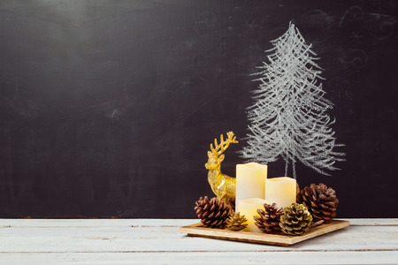 Candles and pine corn decorations on wooden table for Christmas