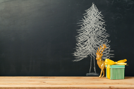 xmas crafts: Background with Christmas tree drawing on chalkboard and gift box Stock Photo
