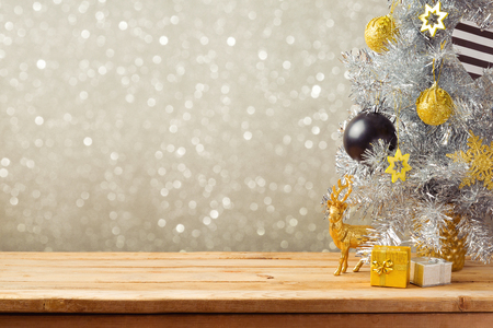 christmas backdrop: Christmas holiday background with Christmas tree and decorations on wooden table. Black, golden and silver ornaments