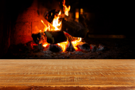 fireplace christmas: Wooden table over fireplace. Christmas holiday concept Stock Photo