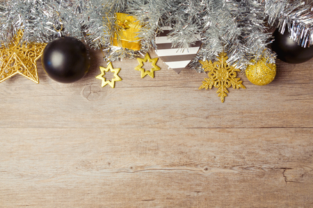 Christmas background with black, golden and silver decorations on wooden table. View from above with copy space