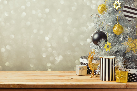 christmas backdrop: Christmas background with Christmas tree on wooden table. Black, golden and silver ornaments