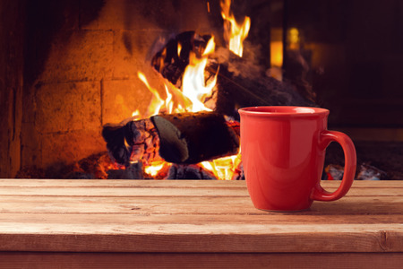 country christmas: Red cup over fireplace on wooden table. Winter and Christmas holiday concept