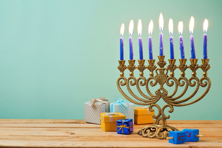 jewish festival: Jewish holiday Hanukkah background with vintage menorah and gift boxes on wooden table
