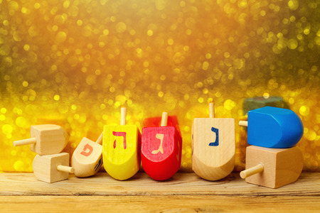 dreidel: Jewish holiday Hanukkah background with spinning top dreidel on wooden table over golden bokeh