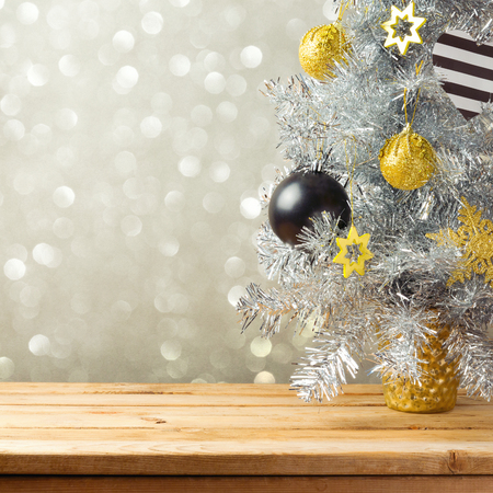 Christmas tree and decorations over bokeh lights background. Black, golden and silver ornaments