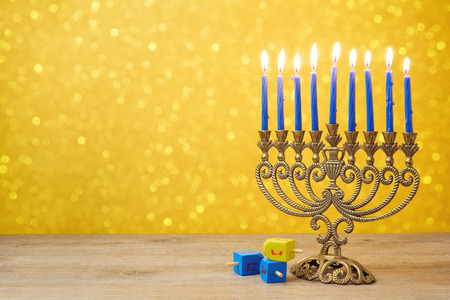Jewish holiday Hanukkah background with vintage menorah and spining top dreidel over lights bokeh
