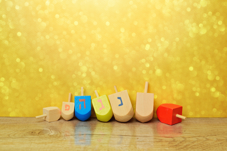 dreidel: Jewish holiday Hanukkah background with spining top dreidel over gold bokeh. Copy space for text Stock Photo