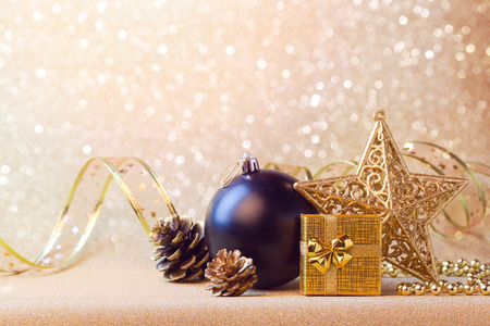 Christmas decorations in black and gold over glitter sparkle background