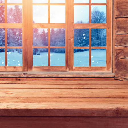 website window: Christmas background with wooden empty table over window and winter nature lanscape. Winter holiday wooden house interior