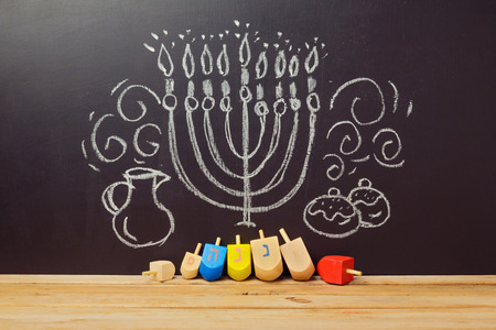 dreidel: Creative Jewish holiday Hanukkah background with spining top dreidel over chalkboard with hand drawing