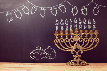 menorah: Jewish holiday Hanukkah background with menorah over chalkboard with hand sketched symbols