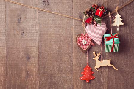 コピー スペースを持つ木製の背景の上にぶら下がって素朴なクリスマスの装飾