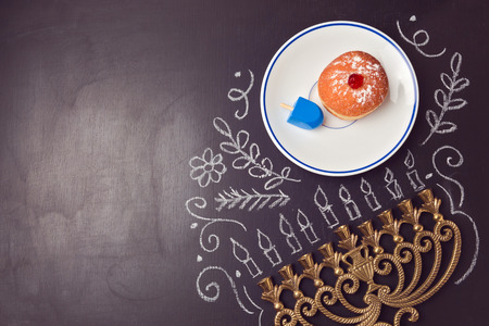 chanukah: Hanukkah holiday background with menorah and sufganiyot over chalkboard. View from above