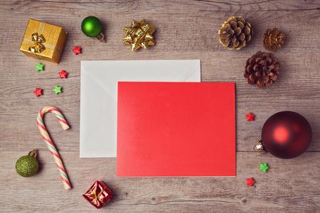 sobres para carta: Tarjeta de felicitación maqueta plantilla con decoraciones de Navidad en el fondo de madera. Vista desde arriba