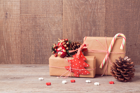 wrappings: Christmas background with gift boxes and rustic decorations on wooden table Stock Photo