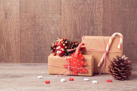 cajas navideñas: Fondo de Navidad con cajas de regalo y decoraciones rústicas en mesa de madera Foto de archivo