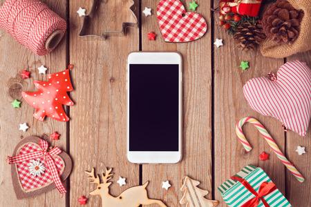 decoracion mesas: Tel�fono inteligente burlan con r�sticas decoraciones de Navidad para la presentaci�n de aplicaciones. Vista desde arriba Foto de archivo