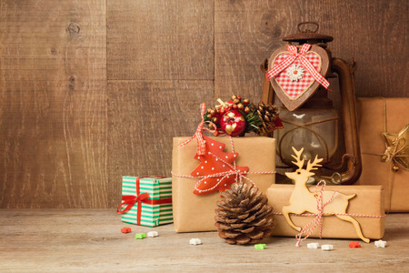 Christmas gift boxes and rustic ornamnets on wooden table 免版税图像