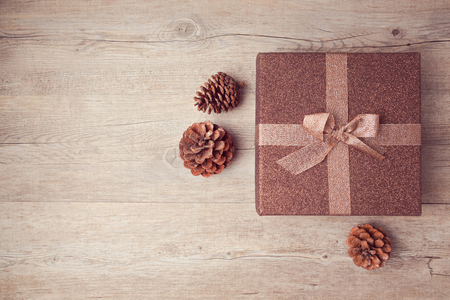 木製の背景にパイン コーンとクリスマス ギフト ボックス。上からの眺め