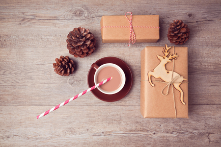 Christmas handmade gift boxes with cup of chocolate and pine corn on wooden table. View from above