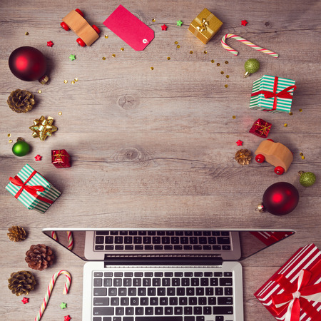 Laptop computer with Christmas decorations on wooden background. Christmas mock up template. View from above