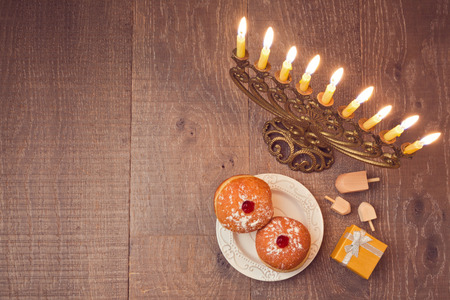 Menorah and sufganiyot on wooden table for Hanukkah celebration. View from above