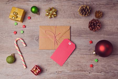 Envelope and gift tag with Christmas decorations on wooden background. View from above 免版税图像