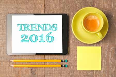 business trends: Business concept of trends for 2016 new year. Digital tablet with coffee cup on wooden desk. View from above.