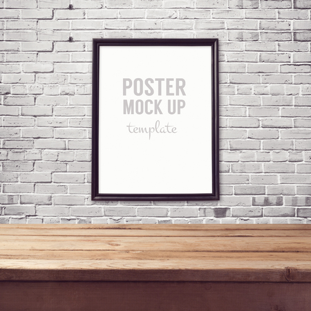 Poster mock up template with wooden table over brick white wall Stock Photo