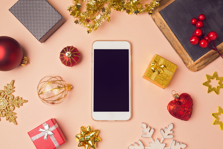 overhead view: Smartphone with Christmas decorations. Christmas mock up template. View from above