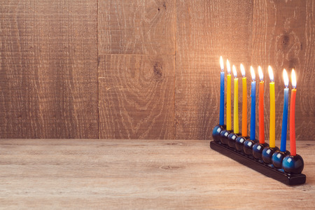 jewish: Jewish Holiday Hanukkah menorah with colorful candles over wooden background