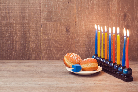 chanukah: Hanukkah menorah with colorful candles and sufganioyt over wooden background Stock Photo