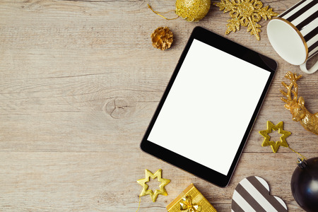overhead view: Digital tablet and Christmas golden decorations on wooden background. View from above