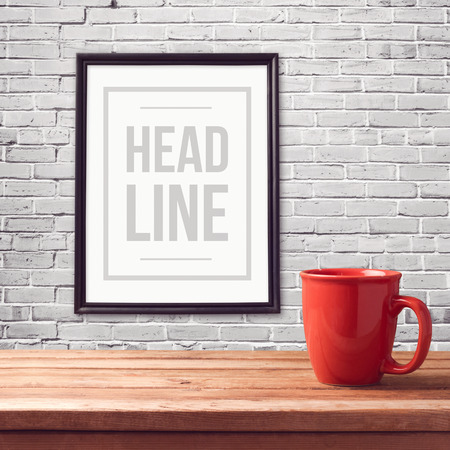 Poster mock up template with red cup on wooden table over brick white wall Stok Fotoğraf - 48540900