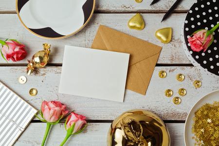 グリーティング カード テンプレートのバラの花と木製の背景の上にチョコレートを模擬。上からの眺め